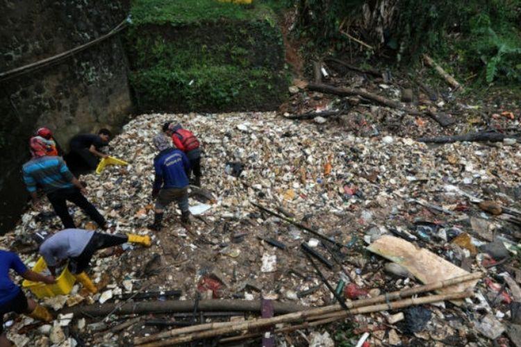 Petugas membersihkan aliran Kali Baru, Cimanggis, Depok, Jawa Barat yang tertutup sampah sepanjang kira-kira 300 meter. Namun, akibat sempitnya akses masuk menuju lokasi, alat berat belum dapat diterjunkan sehingga pengangkutan sampah masih dilakukan secara manual.