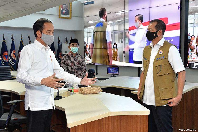 Presiden Jokowi berbicara dengan Ketua Gugus Tugas Percepatan Penanganan Covid-19 Doni Monardo di Graha Badan Nasional Penanggulangan Bencana (BNPB), Jakarta, Rabu (10/6/2020). Ini adalah untuk kali pertama Jokowi mengunjungi kantor Gugus Tugas, sebelumnya rapat dengan jajaran Gugus Tugas biasa dilakukan lewat video conference dari Istana Kepresidenan.