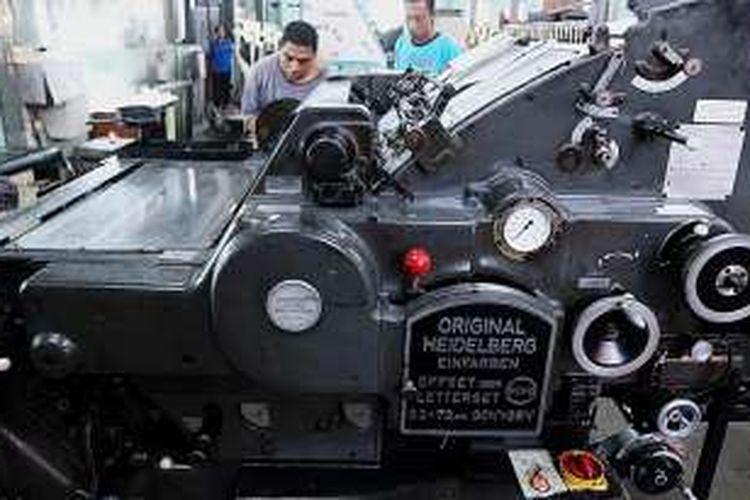 Pekerja memasang kertas pada mesin cetak di percetakan Arnoldus, di jl Nusa Indah, Ende, Nusa Tenggara Timur, Jumat (6/8/2016). Berdiri tahun 1926, percetakan ini masih beroperasi sampai sekarang dan masih mengoperasikan sebagian kecil mesin buatan sekitar tahun 1920-an buatan Jerman.