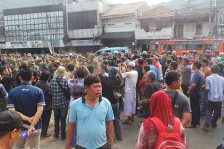 Warga Kampung Pulo berhadap-hadapan dengan petugas. Bentrokan singkat pecah di Jalan Jatinegara Barat, Jakarta Timur. Kamis (20/8/2015).