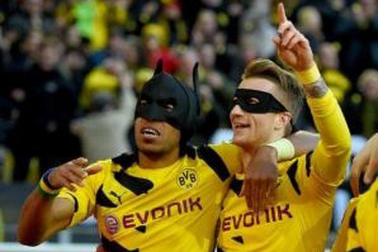 Dua pemain Borussia Dortmund, Pierre-Emerick Aubameyang (kiri) dan Marco Reus (kanan), merayakan gol dengan menggunakan topeng Batman dan Robin pada laga melawan FC Schalke di Signal Iduna Park, Dortmund, Sabtu (28/2/2015).