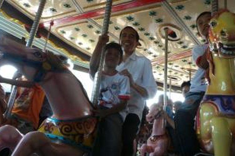 Gubernur DKI Jakarta Joko Widodo Jokowi menaiki komedi putar di Dufan. Dia hadir untuk mengikuti acara Hari Anak Nasional tingkat provinsi di Dufan, Taman Impian Jaya Ancol, Jakarta Utara, Kamis (22/8/2013).