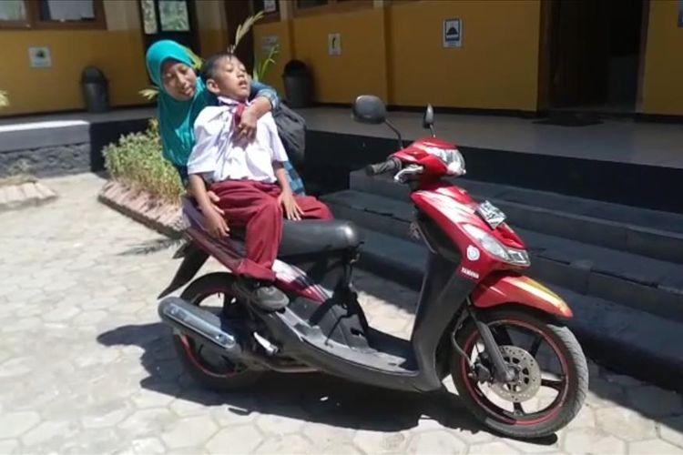 Nampak Tutik mengangkat anaknya Fatta yang mengalami kelumpuhan total pada kedua kakinya sejak kecil. Kendati lumpuh, Fatta memiliki tekad luar biasa mengenyam pendidikan di SDN di Desa Coper, Kecamatan Jetis, Kabupaten Ponorogo.