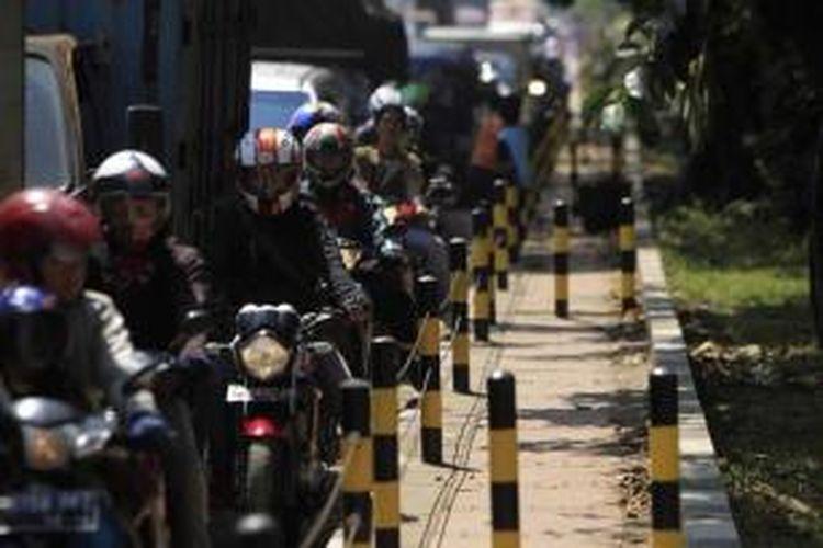 Pengguna sepeda motor tersendat di samping trotoar yang dipasangi tiang besi dan kawat baja di Jalan Raya Bekasi, Cakung, Jakarta Timur, Senin (16/4/2012). Tiang besi dan kawat baja dipasang untuk menutup jalan ke trotoar yang sering dipakai pengguna sepeda motor saat macet.