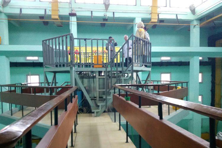 Sejumlah pegawai tengah memeriksa Reaktor Tigra 2000 yang merupakan reaktor nuklir pertama yang dimiliki bangsa Indonesia, berlokasi di Jalan Taman Sari Bandung dan direamikan pada tahun 1965. Reaktor ini berkapasitas 2 MW diperuntukan memproduksi radioisotop dan melakukan analisis dengan Analisis Aktivasi Neutron (AAN) yang bermanfaat dalam melakukan pengujian terhadap sample makanan atau lingkungan.