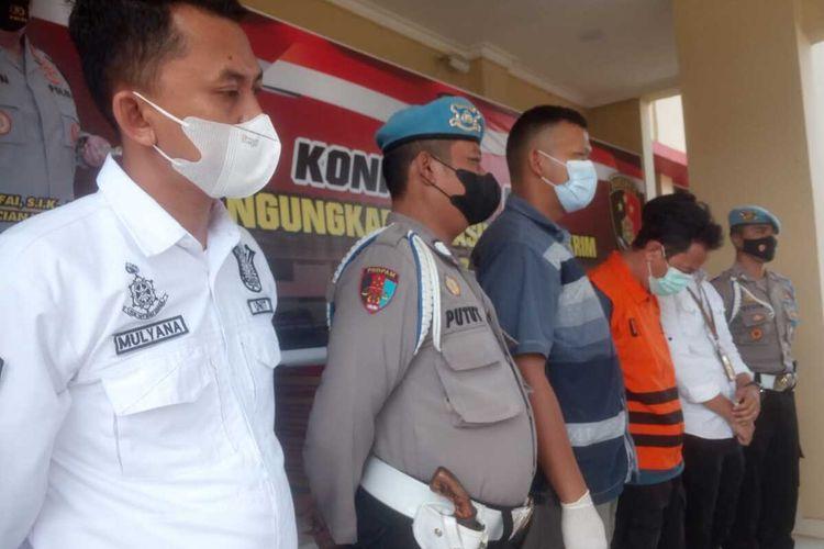 Tersangka JAB diapit sejumlah anggota polisi di Mapolres Cianjur, Selasa (3/5/2021). JAB bersama tersangka lainnya berinisial AR ditetapkan sebagai tersangka kasus pemalsuan surat hasil rapid test antigen.