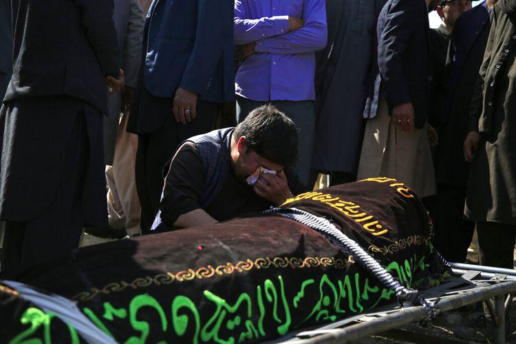 Seorang pria menangis di atas tubuh korban pemboman mematikan pada hari Sabtu di dekat sebuah sekolah, di Kabul, Afghanistan, Minggu (9/5/2021).