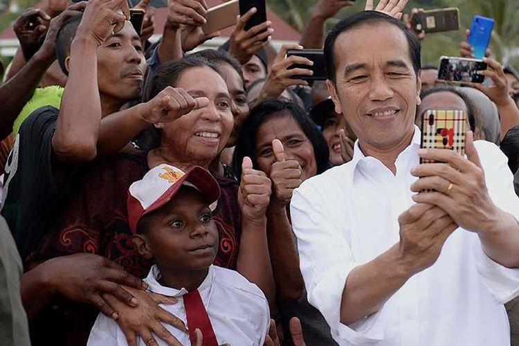 Presiden Joko Widodo atau akrab disapa Jokowi, berswafoto bersama warga yang menyambut kunjungannya di Kabupaten Kaimana, Papua Barat, Minggu (27/10/2019). Dalam kunjungannya, Jokowi dan Ibu Negara Iriana menikmati senja di Kaimana dengan duduk di tepi anjungan Laut Arafuru saat langit mulai memerah.