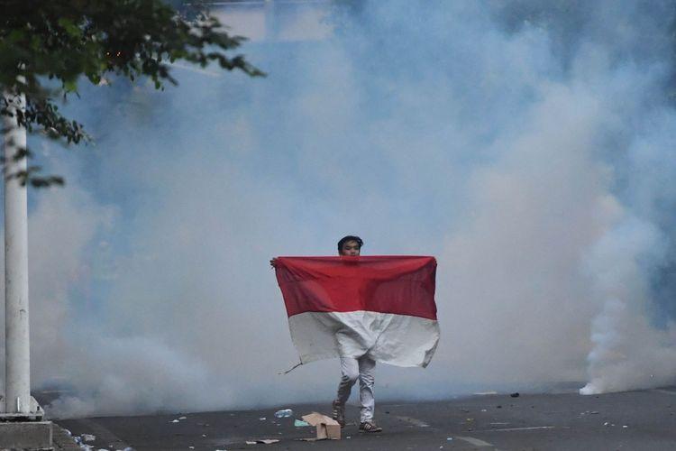 Seorang pengunjuk rasa yang menolak UU KPK hasil revisi dan RUU KUHP membawa bendera Merah Putih di kawasan dekat Kompleks Parlemen, Senayan, Jakarta, Senin (30/9/2019). ANTARA FOTO/Akbar Nugroho Gumay/wsj.