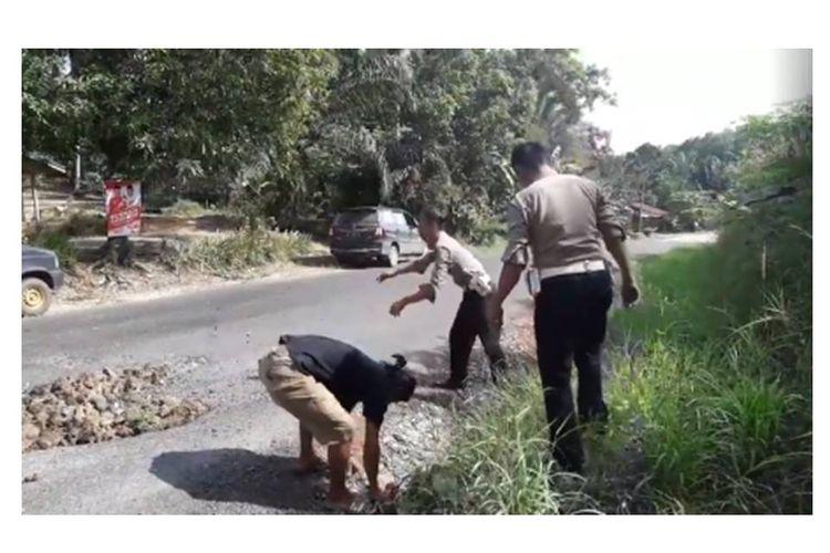 Potongan video yang diunggah pengguna Facebook Aconk Asfiyek mengenai polisi yang menambal jalan berlubang di Paser, Kalimantan Timur, di Paser, Kalimantan Timur.