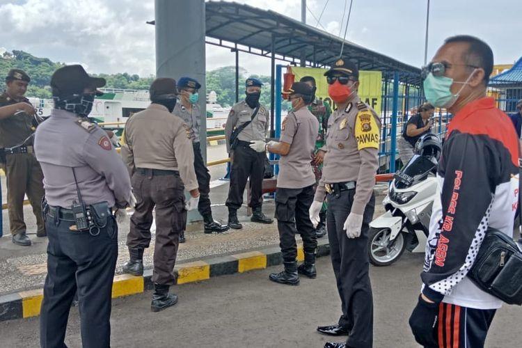 polisi berjaga di Pos Pemeriksaan Pelabuhan Padangbai, Sabtu (28/3/2020).