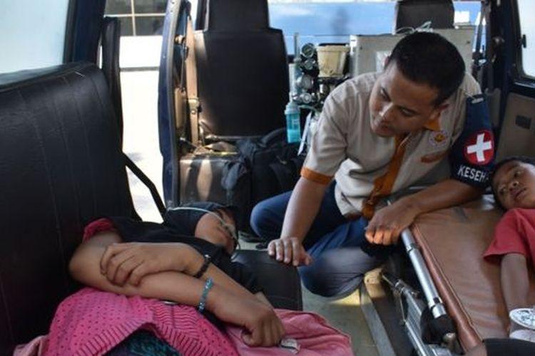 Pengungsi kerusuhan Wamena mendapatkan perawatan kesehatan saat Pesawat Hercules C-130 TNI AU yang membawanya menuju Lanud Halim Perdana Kusuma transit di Lanud Iswahjudi Magetan, Jawa Timur, Kamis (3/10/2019)