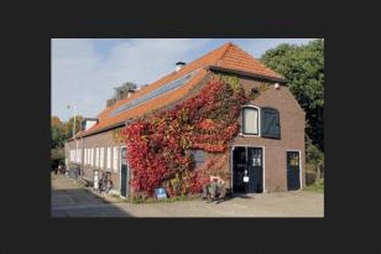Dilihat dari luar, tempat kerja Baas ini tampak hangat dengan genteng berwarna merah tanah liat dan dinding berwarna merah bata.