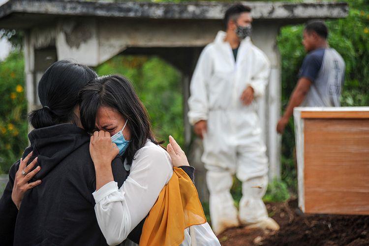 Keluarga menangis saat menyaksikan pemakaman jenazah dengan protokol COVID-19 di TPU Cikadut, Bandung, Jawa Barat, Selasa (15/6/2021). Petugas pikul jenazah mengatakan, pemakaman jenazah dengan protokol COVID-19 di TPU Cikadut mengalami peningkatan sebanyak 20 hingga 30 jenazah per hari dibandingkan dengan bulan lalu yang hanya lima hingga delapan jenazah per hari.