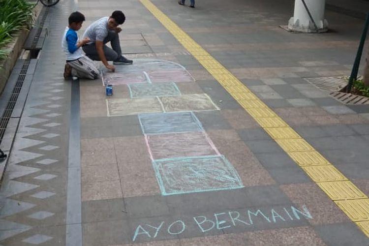 Proses pembuatan permainan tradisional engklek menggunakan kapur di trotoar kawasan Dukuh Atas, Jakarta Pusat.