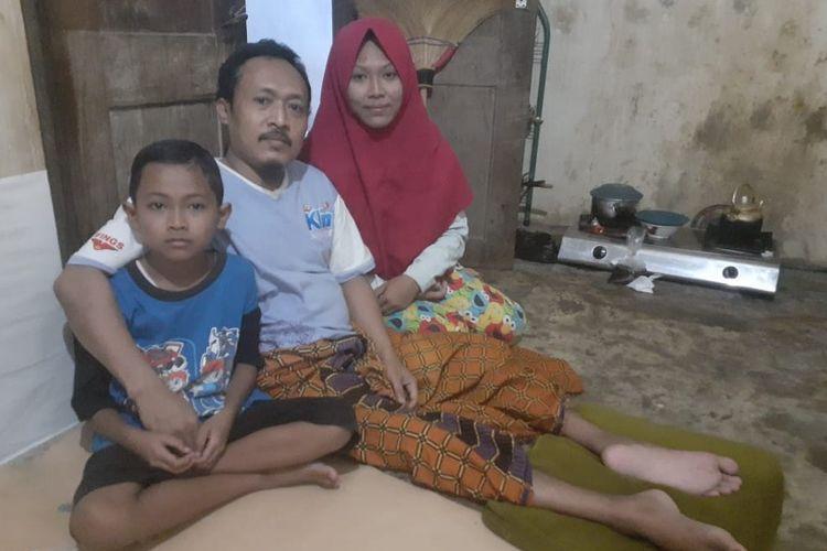 Warja yang mengalami kelumpuhan akibat kecelakaan kerja bersama kedua anaknya yang menghuni bangunan semi permanen berukuran 3×4 meter di Kota Tegal Jawa Tengah, Kamis (7/5/2020)