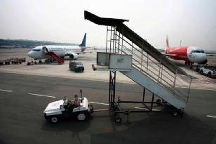 Petugas groundhandlilng JAS Airport Services tengah mempersiapkan keberangkatan pesawat maskapai internasional di hari perdana pengoperasian Bandara Internasional Kualanamu, Deli Serdang, Sumut, Kamis (25/7/2013).
