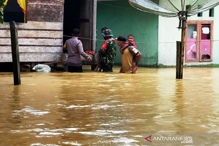 Dokumentasi - Prajurit TNI membantu mengevakuasi masyarakat yang terdampak banjir akibat meluapnya aliran sungai di Kecamatan Tripa Makmur, Kabupaten Nagan Raya, Aceh, Selasa (6/7/2021).