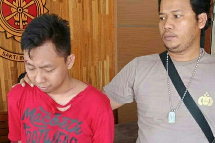 Pelaku (baju merah) saat diamankan kepolisian (22/10/2018)