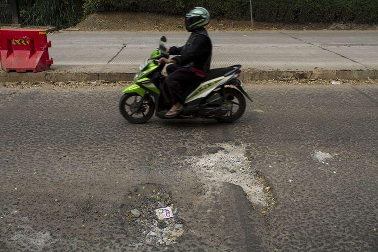 Pengendara melintasi jalan berlubang di Grand Depok City (GDC) Grand Depok City, Depok, Jawa Barat, Rabu, (11/12/2019). Beberapa jalan sepanjang GDC masih berlubang dan bergelombang.