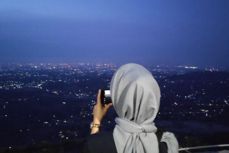 Wisatawan mengabadikan kerlip lampu Yogyakarta dari Puncak Becici.