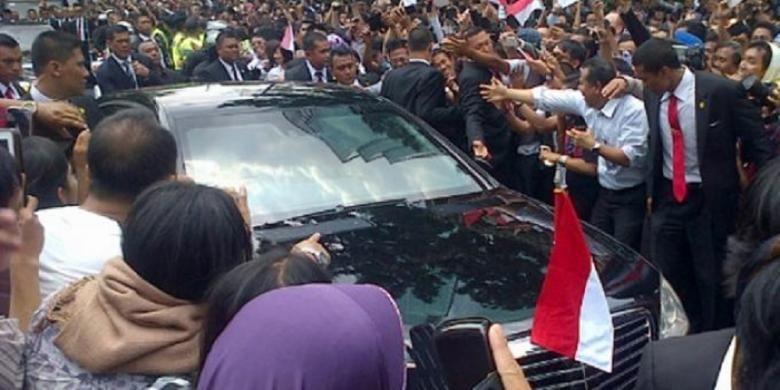 Massa mendekati mobil RI 1 yang ditumpangi Presiden Joko Widodo di Jalan Sudirman, Jakarta Pusat, Senin (20/10/2014).