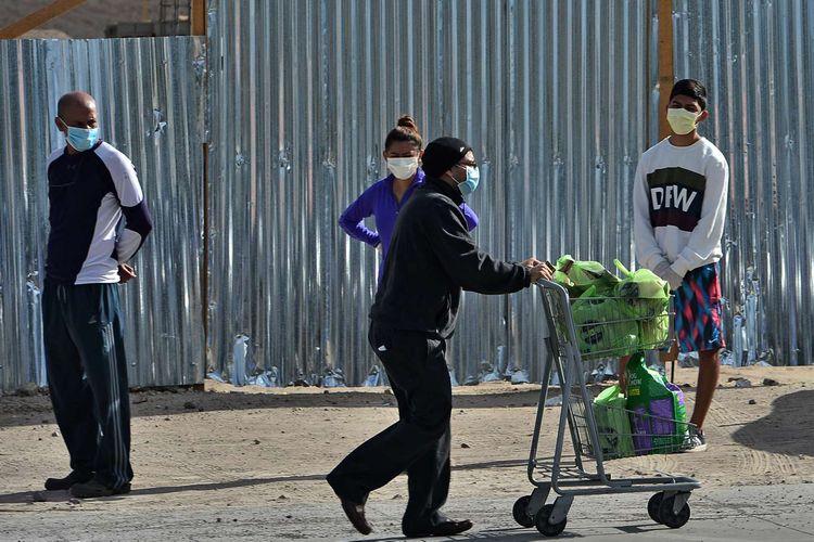 Seorang pria yang usai berbelanja melewati sejumlah warga yang mengantre dengan menjaga jarak aman saat akan berbelanja di supermarket, di Tegucigalpa, Honduras, 19 Maret 2020. Menjaga jarak aman antar warga merupakan salah satu cara yang dianjurkan untuk mencegah penyebaran virus corona.