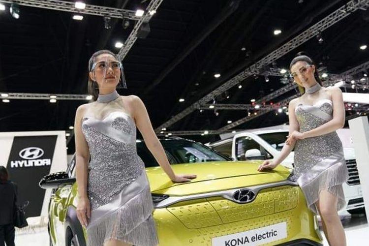 Model di BIMS 2020 mengenakan face mask ketika tampil bersama mobil yang dipamerkan selama pameran.