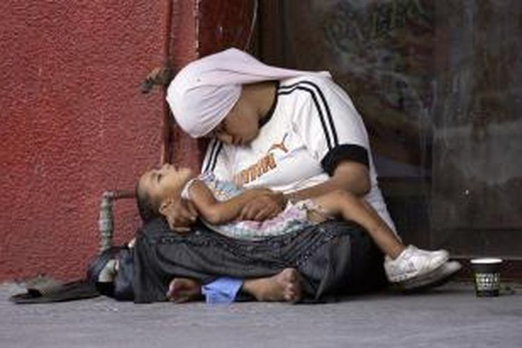 Pengungsi Suriah dan seorang anaknya terlihat di jalanan Lebanon. Gambar diambil pada 18 Juli 2013. Seiring tak kunjung usainya konflik di Suriah, jutaan warga mereka mengungsi dan menyesaki negara-negara tetangga di Timur Tengah maupun Eropa.
