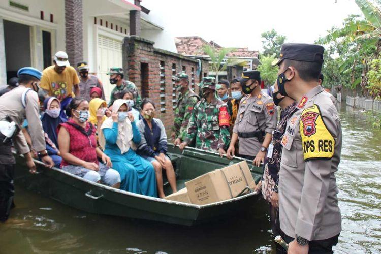 Dandim 0722 Kudus Letkol Kav Indarto dan Kapolres Kudus AKBP Aditya Surya Dharma beserta jajarannya ikut turun tangan mengevakuasi warga yang masih bertahan di tengah genangan banjir di Desa Payaman, Kecamatan Mejobo, Kabupaten Kudus, Jawa Tengah, Selasa (9/2/2021).