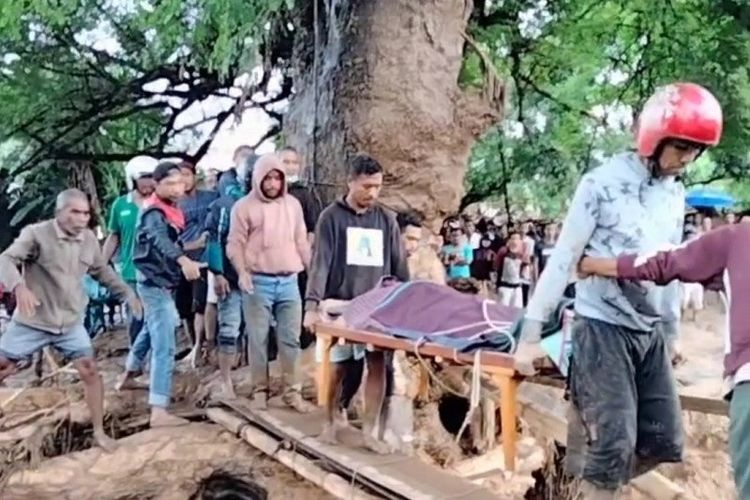 A number of residents while carrying their bodies through an emergency bridge built at the flash flood site in the Waiwerang and surrounding areas in East Adonara District, Adonara Island, East Flores Regency, NTT, on Sunday, April 4.