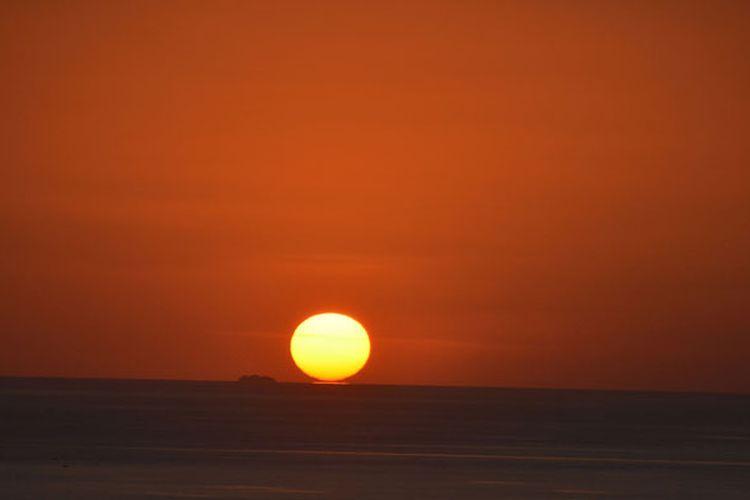 Matahari menyentuh air laut di ujung barat Pulau Flores saat terbenam, Senin (28/8/2017). Ini merupakan salah satu keunikan saat matahari terbenam di Manggarai Barat, Nusa Tenggara Timur.