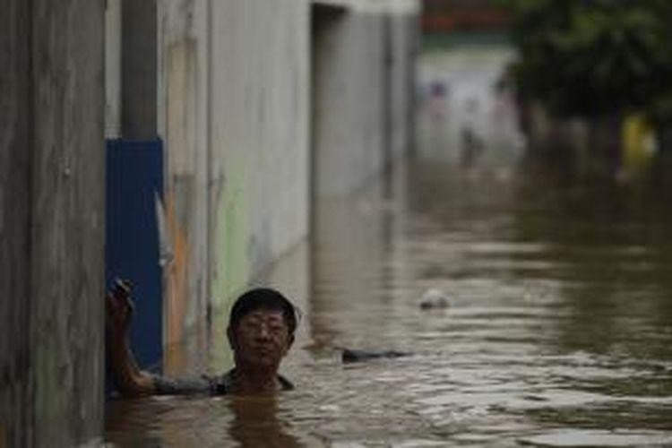 Warga beraktivitas di tengah banjir yang melanda kawasan Bidara Cina, Jakarta, Senin (13/1/2014). Hujan yang melanda Jakarta sejak Minggu pagi ditambah meluapnya sungai Ciliwung akibat banjir kiriman dari Bogor mengakibatkan sejumlah kawasan ini terendam banjir sejak Minggu malam. KOMPAS IMAGES/RODERICK ADRIAN MOZES