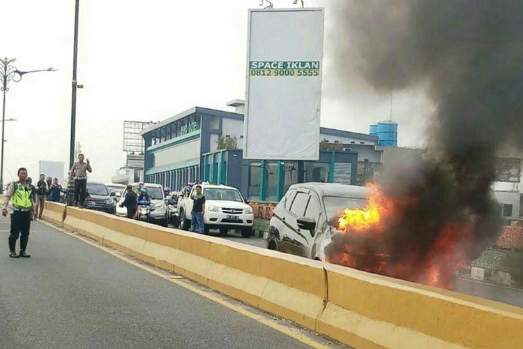 Kebakaran mobil Mitsubishi Expander di atas fly over Jalan Jenderal Sudirman, Kota Pekanbaru, Riau, Sabtu (31/8/2019).