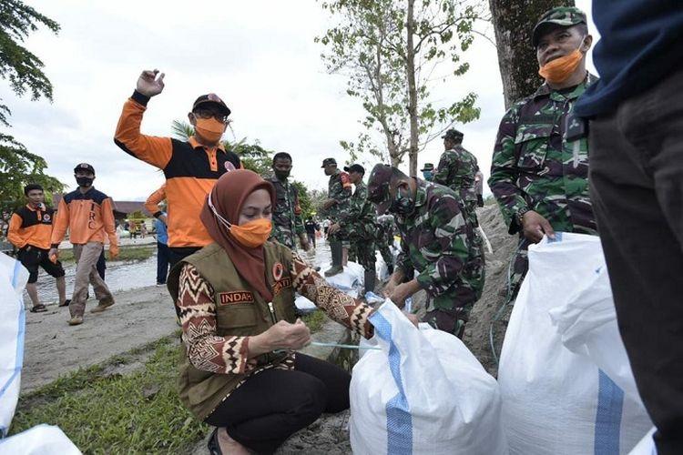 Bupati Luwu Utara Indah Putri Indriani, saat memimpin gotong royong pembuatan tanggul darurat, di bantaran Sungai Masamba, Kamis (2/7/2020).