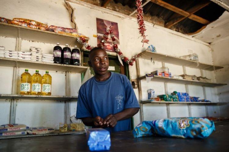 Solomon Chakauya, menunggu pelanggan di toko kelontongnya, di distrik Chinamhora, Zimbabwe. Foto ini diambil pada 10 Desember 2018. (AFP/JEKESAI NJIKIZANA)