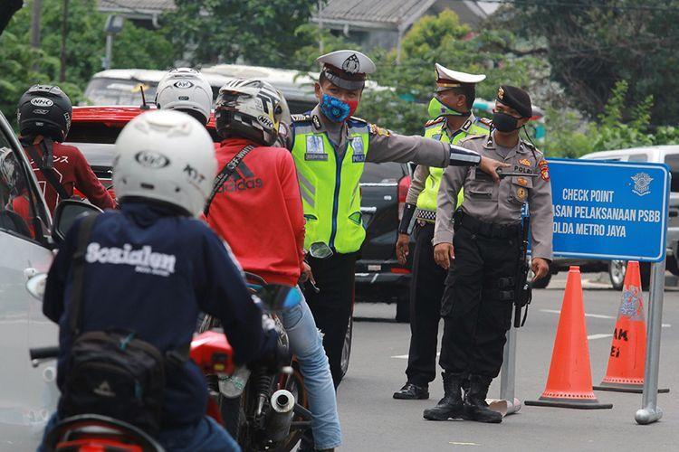 Petugas kepolisian menghalau pengendara motor yang akan masuk ke Jakarta karena tidak mengenakan masker saat penerapan Pembatasan Sosial Berskala Besar (PSBB) di perbatasan Tangerang Selatan dengan DKI Jakarta, Sabtu (11/4/2020). Pada hari kedua pelaksanaan penerapan PSBB masih banyak pengendara yang melanggar aturan dimana masih ada yang tidak mengenakan masker, pembatasan duduk penumpang mobil serta jumlah penumpang mobil yang melebihi aturan.(ANTARA FOTO/MUHAMMAD IQBAL)