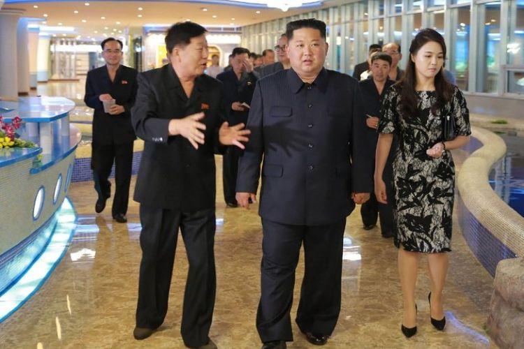 Pemimpin Korea Utara Kim Jong Un (tengah) dan istrinya, Ri Sol Ju (kanan), mengunjungi restoran seafood di dekat Sungai Taedong yang baru dibangun di Pyongyang. (KCNA via KNS/AFP)