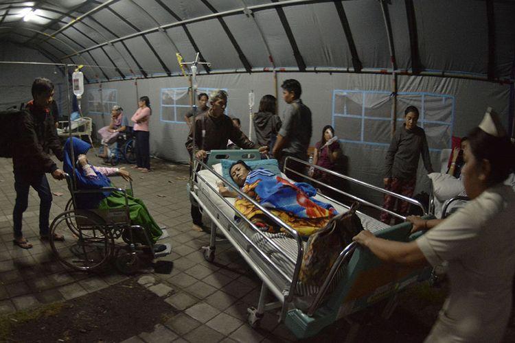 Petugas medis memindahkan pasien dari ruang perawatan ke tenda usai terjadi gempa di RSUP Sanglah, Denpasar, Bali, Minggu (19/8/2018). Sejumlah pasien di rumah sakit tersebut dipindahkan ke tenda dan lorong rumah sakit pascagempa bermagnitudo 7 yang berpusat di Lombok Timur pada Minggu malam.