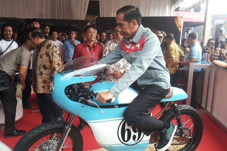 Presiden Joko Widodo menaiki salah satu sepeda motor Honda CB 125 lawas yang dipamerkan di stan Increase saat berlangsungnya hari pertama pameran Indonesia International Motor Show (IIMS) 2018, di JIExpo Kemayoran, Jakarta, Kamis (19/4/2018). Motor yang dimodifikasi bergaya caferacer merupakan milik putra sulung Jokowi, Gibran Rakabuming.