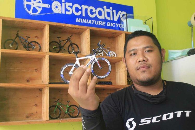 Yudi Hermawan, salah satu pemuda yang tergabung dalam Aiscreative_miniaturbicyle menunjukkan miniatur sepeda buah tangan mereka.