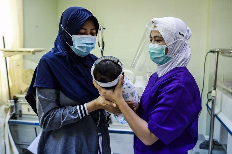 Perawat merawat bayi yang baru lahir di ruangan Perina di Rumah Sakit Ibu dan Anak (RSIA) Tambak, Jakarta Pusat, Sabtu (23/5/2020). Rumah Sakit Ibu dan Anak (RSIA) menerapkan kebijakan baru berupa pemakaian face shield atau pelindung wajah untuk bayi yang sedang mendapat perawatan maupun yang baru dilahirkan di RS tersebut. Hal tersebut dilakukan untuk mencegah terjadinya penularan virus corona jenis baru atau SARS-CoV-2 yang menyebabkan penyakit Covid-19.