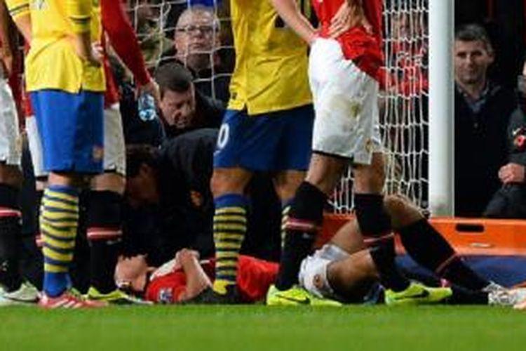 Kapten Manchester United, Nemanja Vidic, mendapatkan perawatan setelah berbenturan dengan kiper David de Gea pada laga melawan Arsenal di Stadion Old Trafford, Manchester, Minggu (10/11/2013).