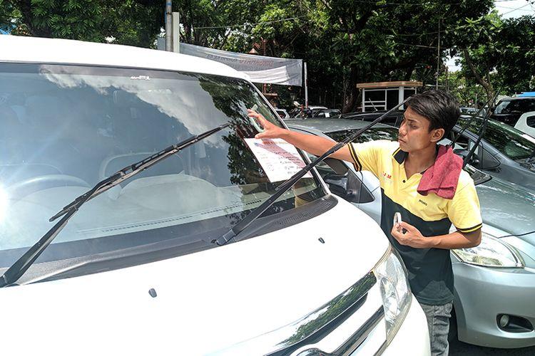 Seorang pedagang memasang kertas berisi spesifikasi mobil yang akan dijual di bursa mobil Sriwedari, Solo, Jawa Tengah, Minggu (15/12/2019). Setiap Minggu ratusan mobil bekas dijajakan di Bursa Mobil Sriwedari.
