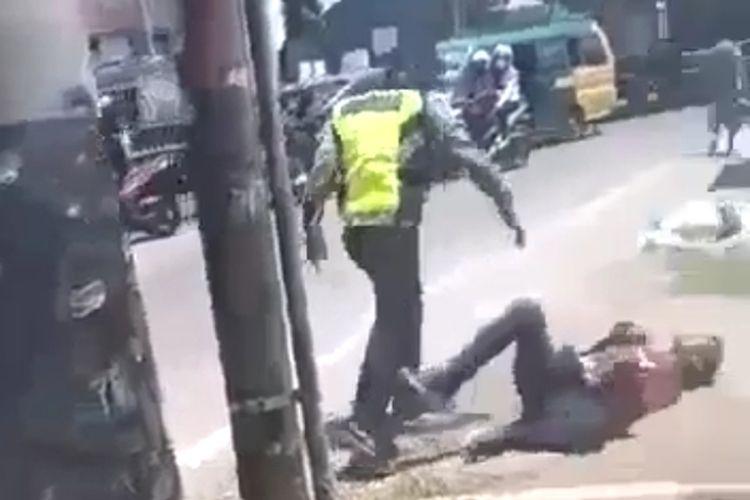 Tangkapan layar video seorang oknum polisi Satlantas Polresta Deli Serdang memukul pengendara sepeda motor yang melanggar lalu lintas. Oknum tersebut kini dicopot dari jabatannya.