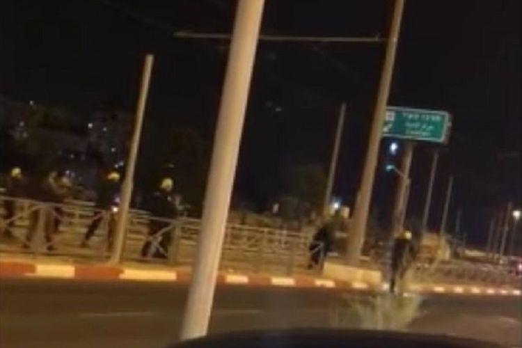 Polisi Israel mengerubungi seorang wanita yang tertembak kakinya setelah tidak merespon peringatan mereka Minggu (27/5/2018).