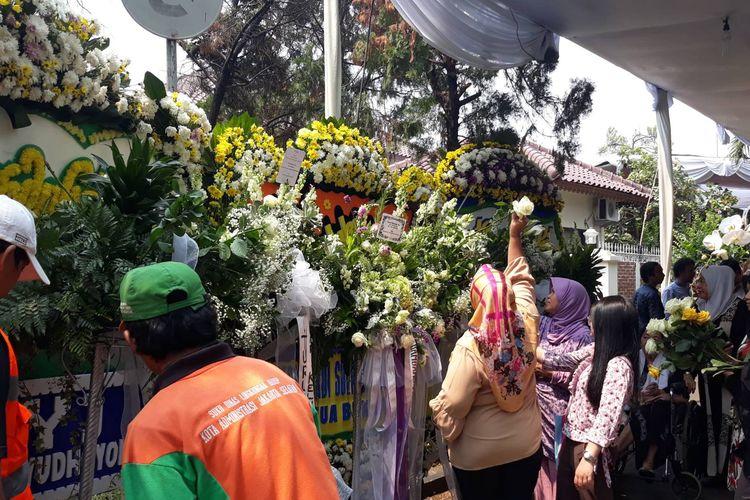 Pelayat di rumah duka BJ Habibie menjumput bunga dari papan karangan usai upacara penyerahan jenazah.