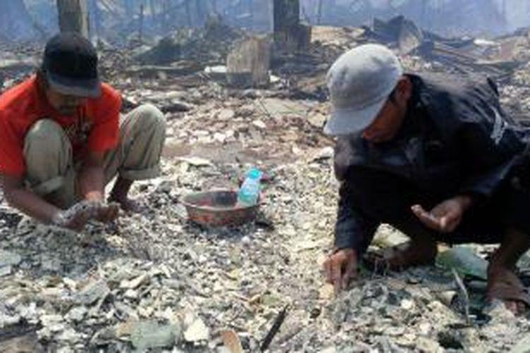 Dua warga terlihat mengais puing bekas kebakaran yang menghanguskan puluhan ruko di komplek Pasar Tengah, Pontianak (22/8/2015)