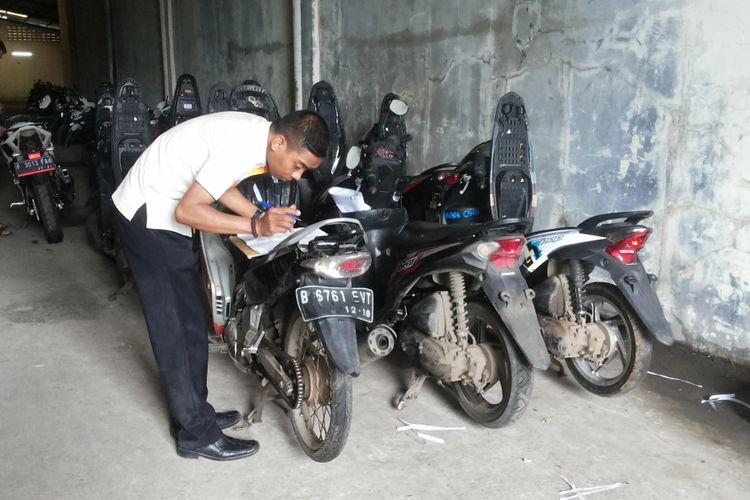 Ilustrasi: Seorang petugas mengecek motor-motor yang ditarik dan disimpan di gudang penyimpanan milik salah satu perusahaan pembiayaan di Tapos, Depok, Senin (5/2/2018).