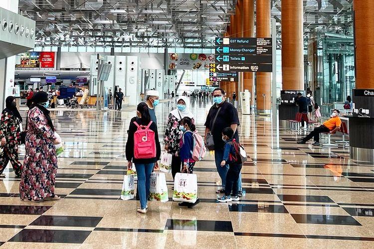 Segelintir penumpang pesawat terlihat di Terminal 3 Keberangkatan Bandara Internasional Changi, Singapura, Minggu sore (17/01/2021)